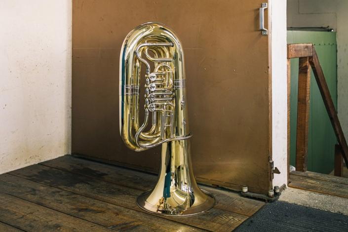 Eine hochglanzpolierte, messingfarbene Tuba steht vor einer Schiebetür.