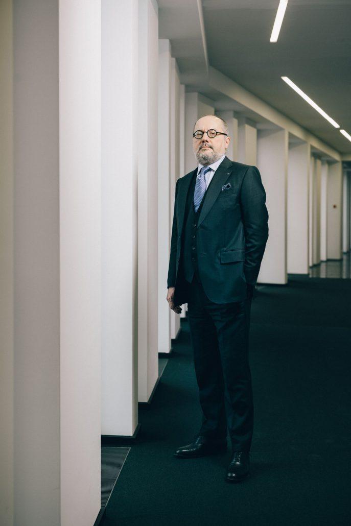 CEO der Linde AG, Aldo Belloni stehend in einem Ganz mit weißen Säulen und schwarzem Teppich.