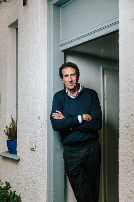 Philosoph Julian Nida-Rümelin mit verschränkten Armen in einem hölzernen Türrahmen seines Büro stehend.