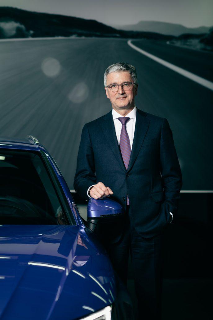Rupert Stadler mit Hand auf dem Außenspiegel eines blauen Audi A4 Quattro vor dem Bilder einer Bergstraße.