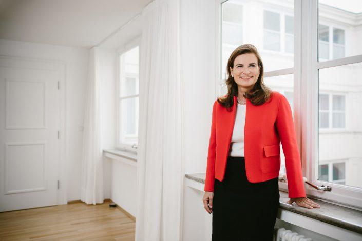 Ann-Katrin Achleitner stehend vor einem Fenster in rotem Blazer.