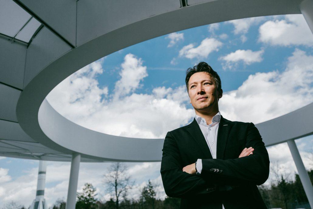Dirk Hoke mit verschränkten Armen unter einer großen runden Öffnung des Vordachs zum Verwaltungsgebäude, durch das man den Himmel sehen kann.