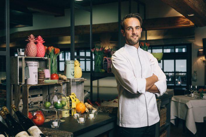 Mike Emmerz, Küchenchef bei Käfer stehend mit verschränkten Armen vor der Küche in der Käfer Schänke.