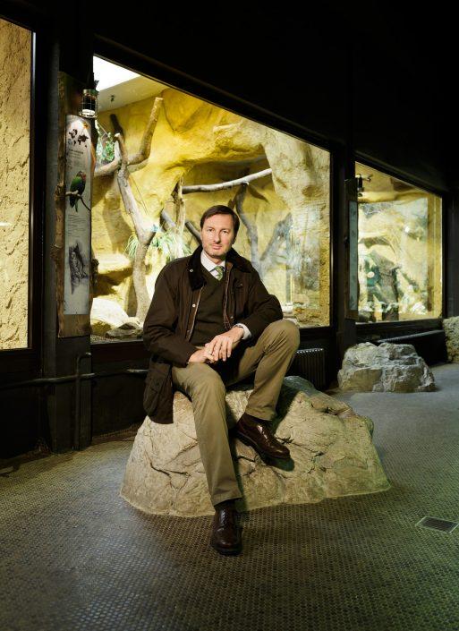 Andreas Knieriem sitzend auf einem großen Stein im Fledermaushaus des Tierpark Hellabrunn.