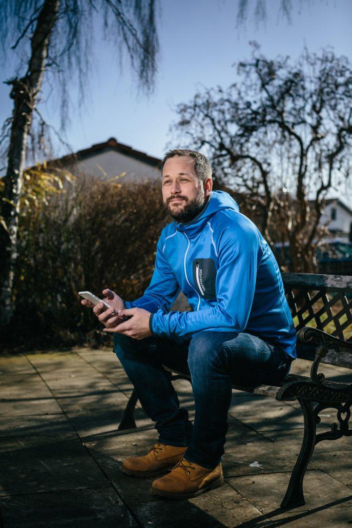 Alexander Krapp in blauem Hoodie sitzend auf einer Parkbank mit Handy in der Hand.