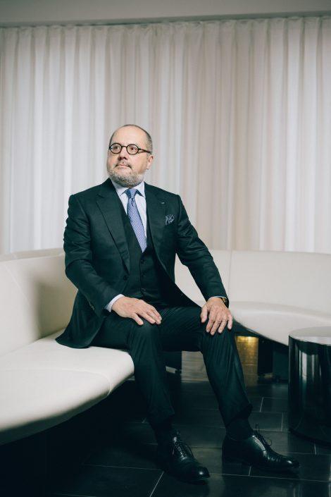 Aldo Belloni sitzend auf einer weißen Ledercouch.