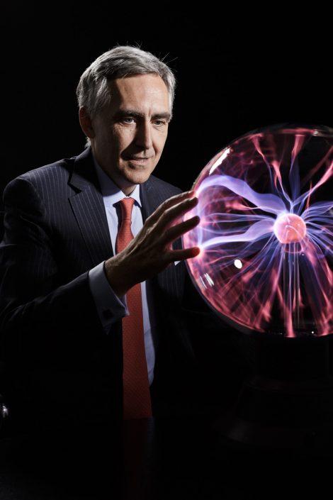 Peter Löscher fasst eine leuchtende Plasmakugel mit den Händen an.