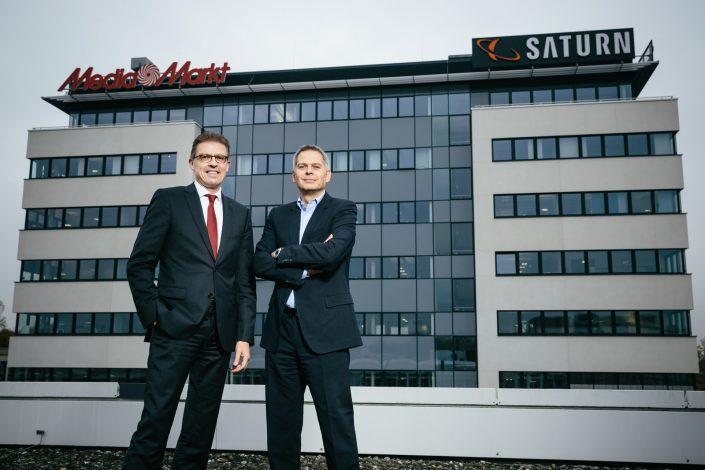 CEO und CFO der Media Saturn Holding bei einem Bürogebäude des Unternehmens.