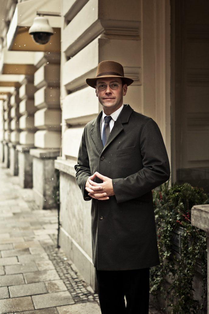 Portrait von James Murdoch mit Mantel und Hut