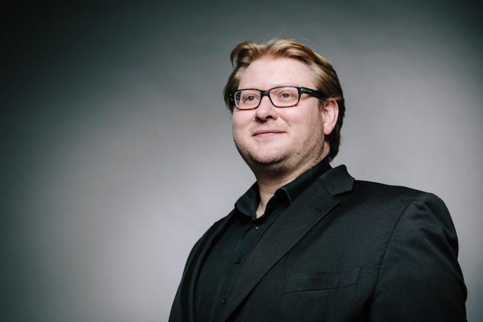 Portait von Unternehmensberater Ansgar Oschwald in schwarzem Anzug vor neutral grauem Hintergrund