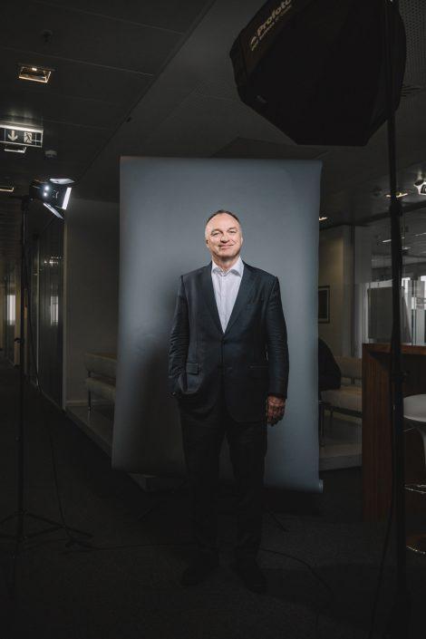 Thomas Ebeling stehend vor neutral grauem Hintergrund mit dem Lichtsetup von Thorsten Jochim