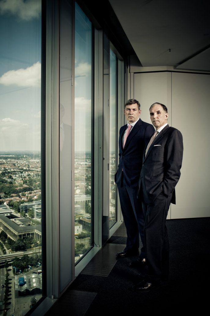 Zwei Männer in Anzügen stehend vor bodenlangen Fenstern im 30. Stockwerk mit Blick auf den Münchner Norden.