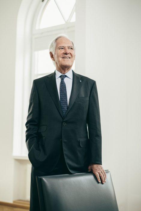 Roland Berger stehend vor einem schwarzem Sessel in einem hellem Büro.