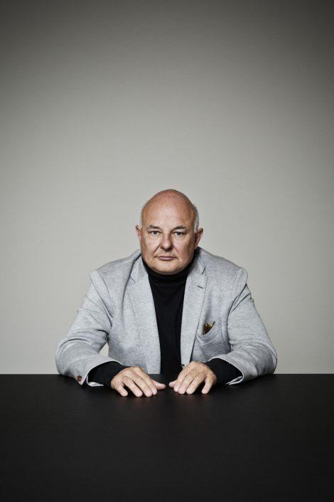 Sitzender Rolf Sachs an einem schwarzem Tisch vor hellgrauem Hintergrund.
