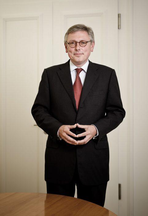 Bankier Stephan Rupprecht stehend mit Merkel-Raute.