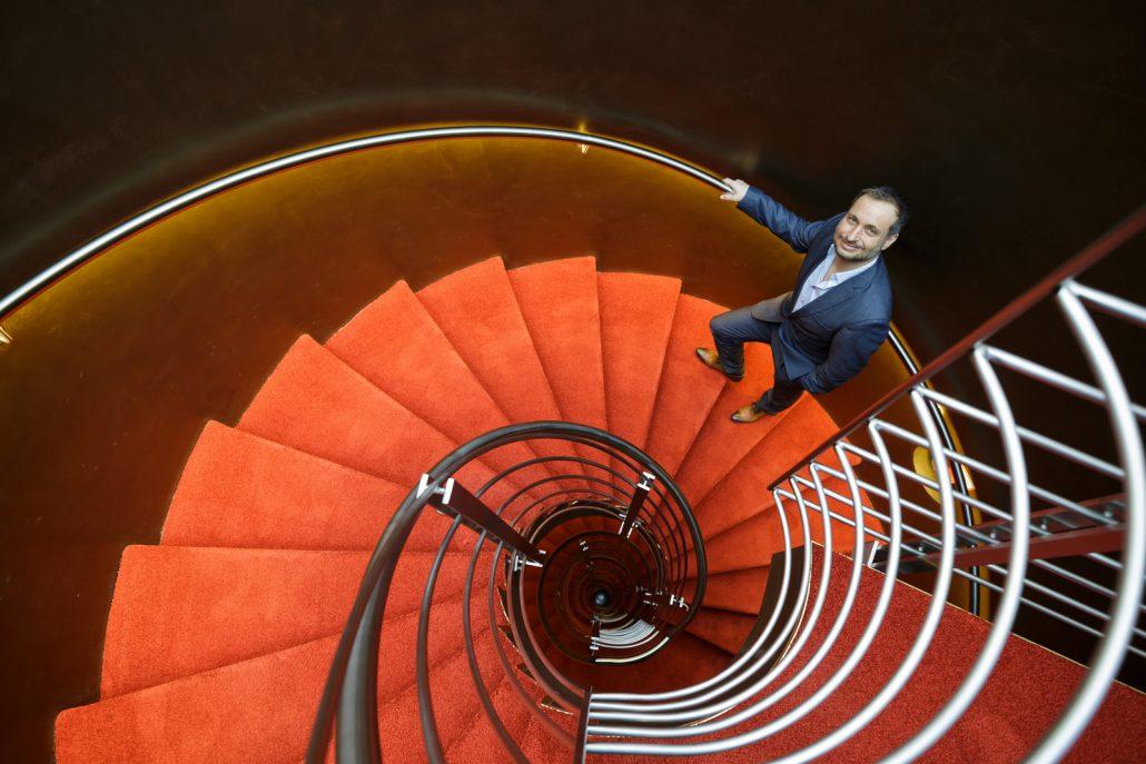 Max M. Schlereth stehend in einem mit rotem Teppich belegten Wendeltreppenhaus.