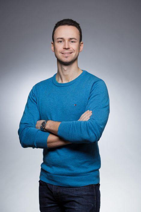 Alexander Simonov mit blauem Pulli und verschränkten Armen im Portrait