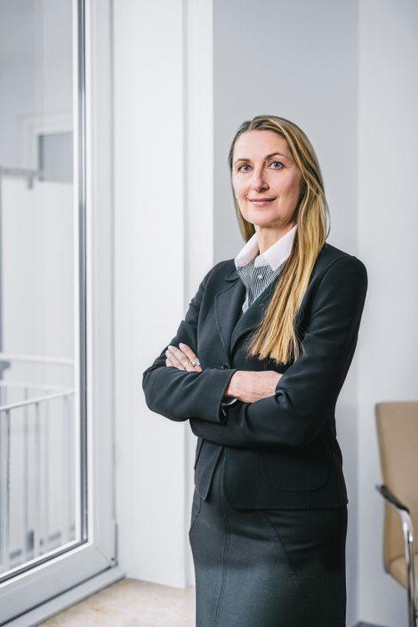 Daniela Spohn, Rechtsanwälting in dunklem Kostüm mit verschränkten Armen vor einem Fenster stehend.