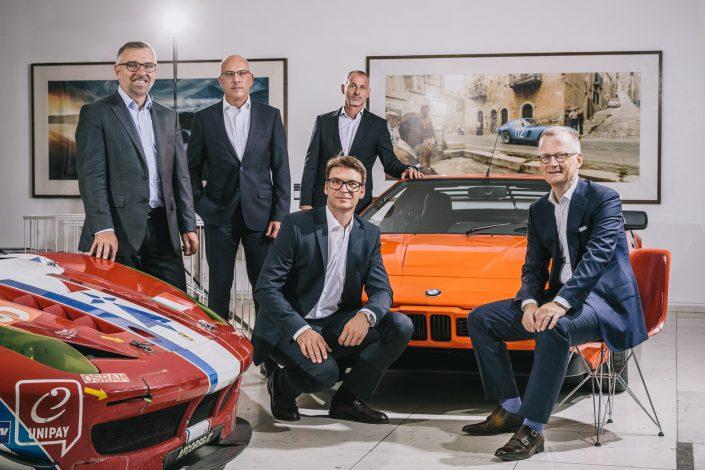 Gruppenfoto mit fünf Managern der Strategy Engineers vor einem Organgenen BMW M1.
