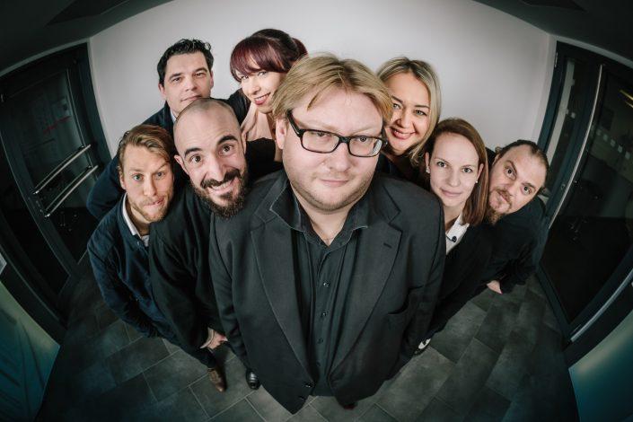 Fisheye Aufnahme von acht Unternehmensberatern der Ansgar Oschwald Unternehmensberatung in München.