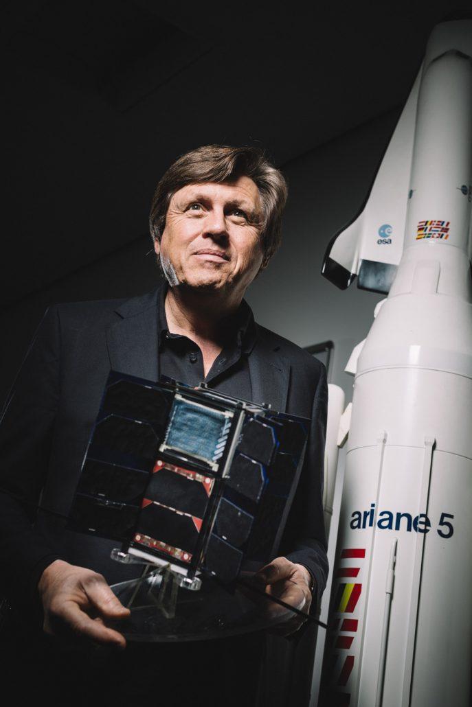 Astronaut Ulrich Walter stehend vor einem Ariane Raketenmodel.