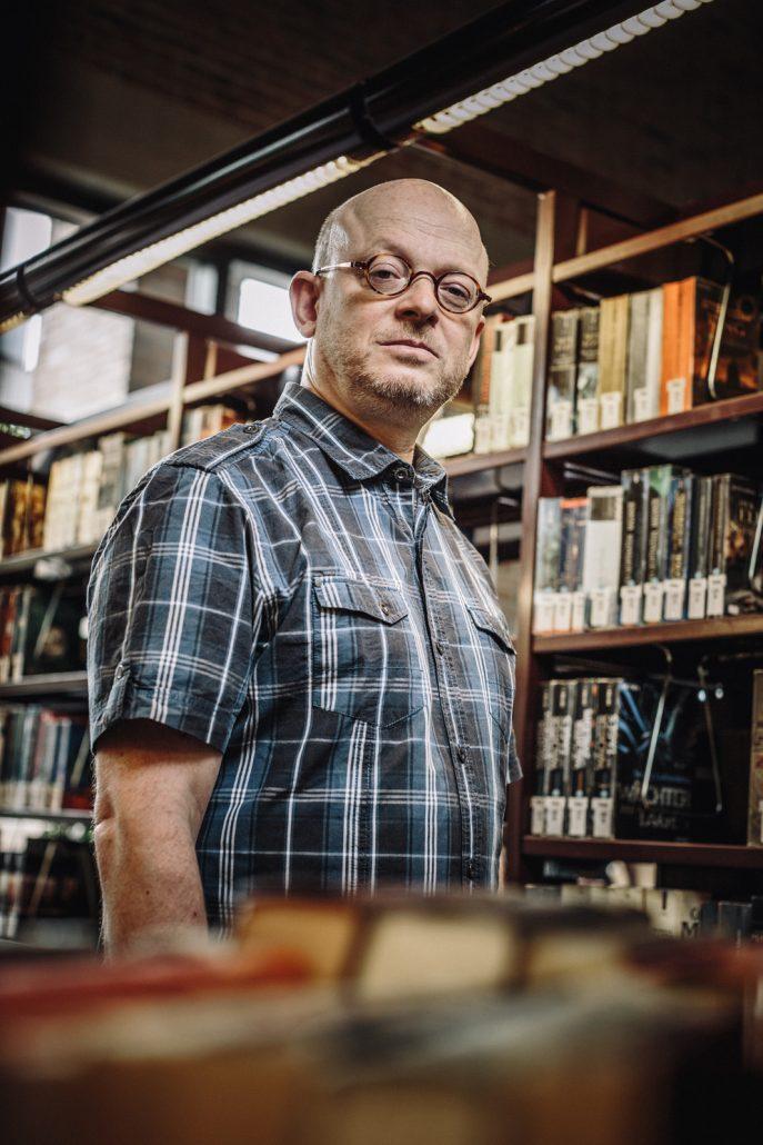 Timur Vermez blickt in die Kamera. Er steht zwischen Bücherregalen der Münchner Stadtbücherei.