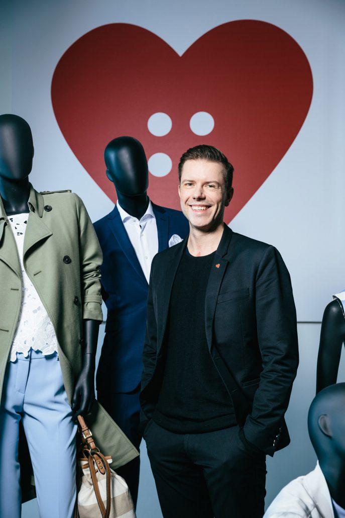 Christian Greiner mit dunklem Anzug zwischen Schaufensterpuppen vor rotem Herz.