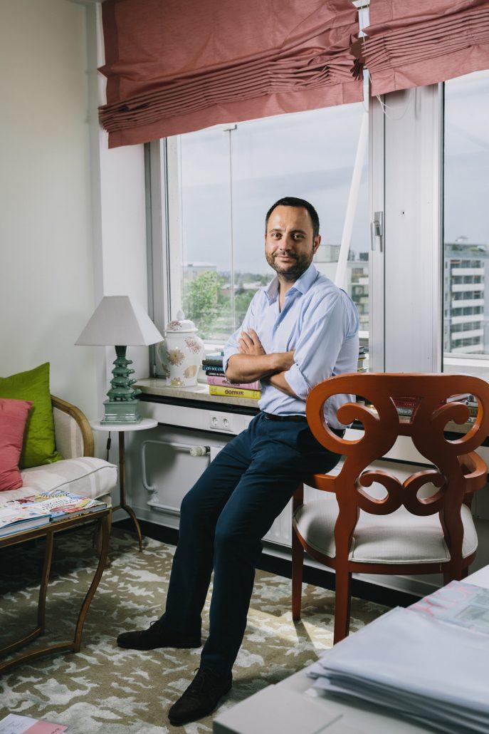 Stefan Smalla auf Armlehne eines alten Stuhls sitzend vor dem Fenster seines Büros in München.