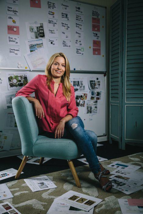 Delia Fischer auf Sessel zwischen ausgedruckten Konzepten und Entwürfen sitzend.