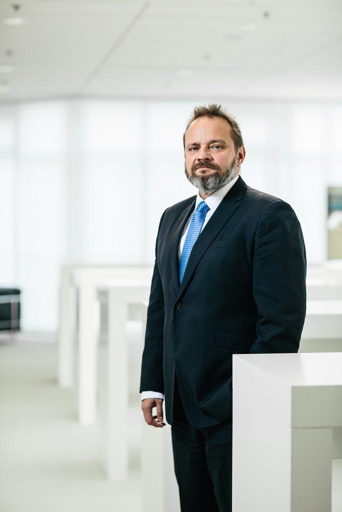 Johannes-Jörg Riegler stehend mit blauer Krawatte und dunklem Anzug vor weißen Stehtischen in hellem Büroambiente.