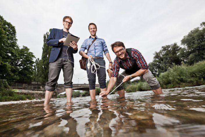 Die drei lässig gekleideten Geschäftsführer von Polarstern Energie stehend im Wasser der Isar mit Kabel und iPad in der Hand.