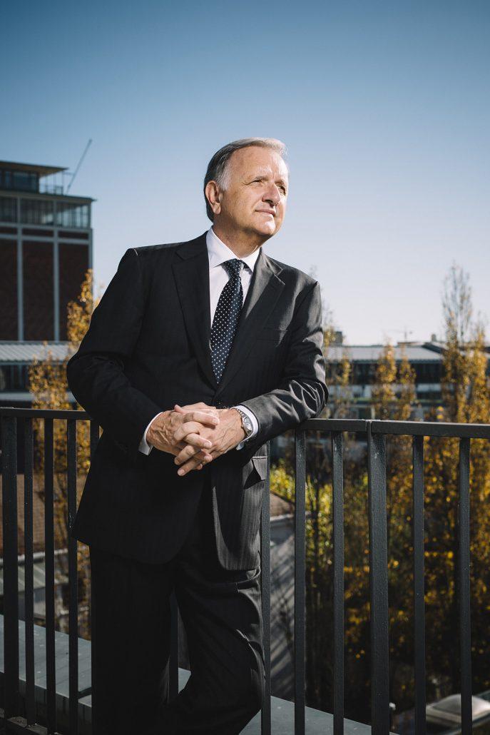 Unternehmensberater Norbert Wieselhuber in dunklem Anzug und Krawatte auf der Dachterasse seines Unternehmens in München.