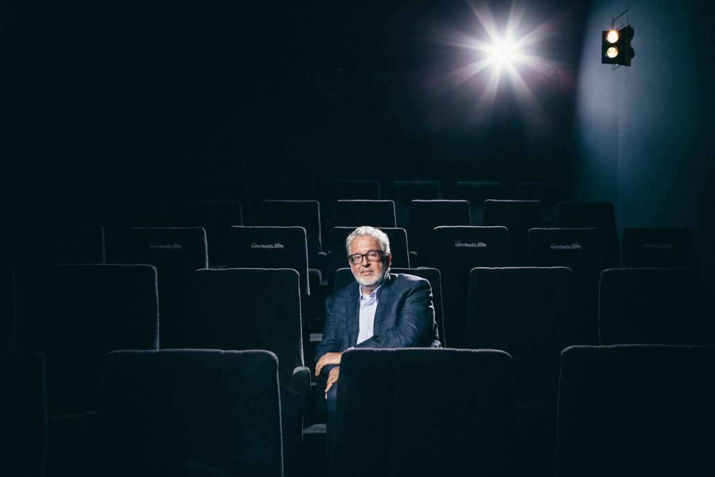 Martin Moszkowicz sitzend im schwarzen Kinosessel des hauseigenen Kinosaals.