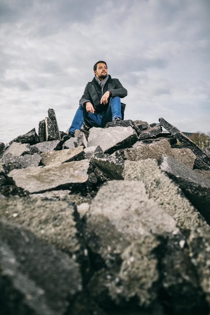 Mr. Königsklasse Martin Grosse sitzend auf einem Haufen Teerplattenreste.
