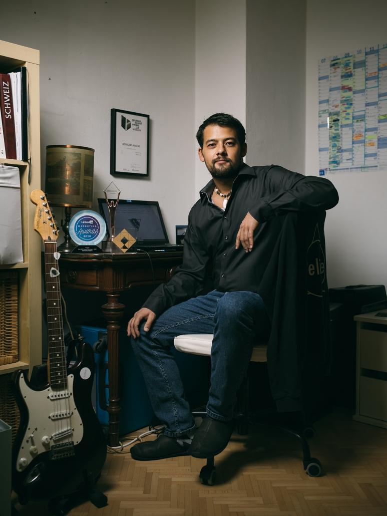 Mr. Königsklasse Martin Grosse sitzend an einem kleinem Schreibtisch in seinem Appartment mit Awards darauf.