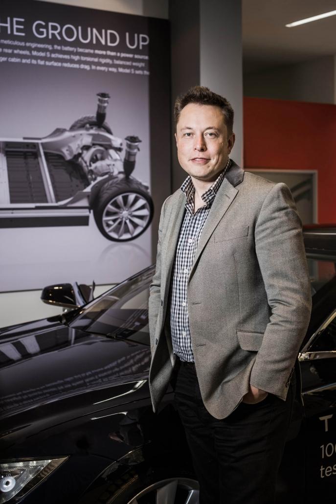 Elon Musk mit Sakko vor einem Tesla Model S.