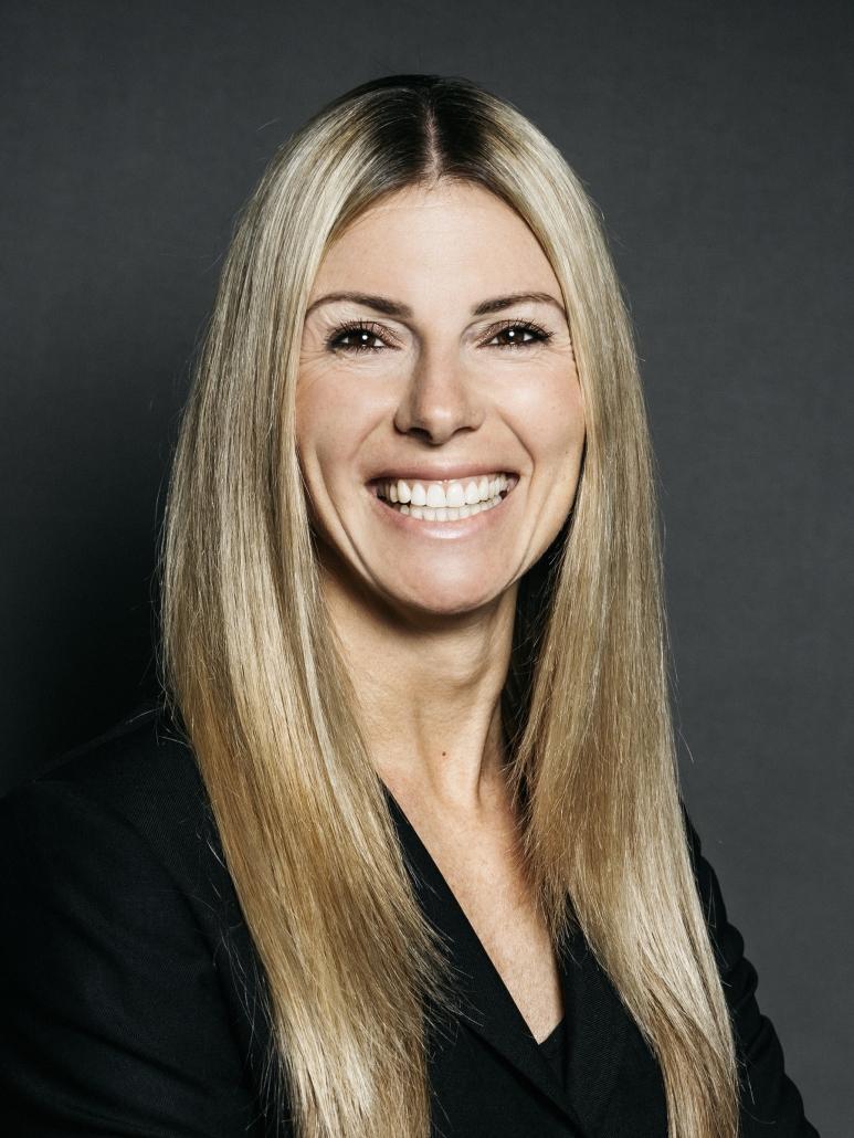 Kathrin Buvac vor neutral grauem Hintergrund lacht in die Kamera.