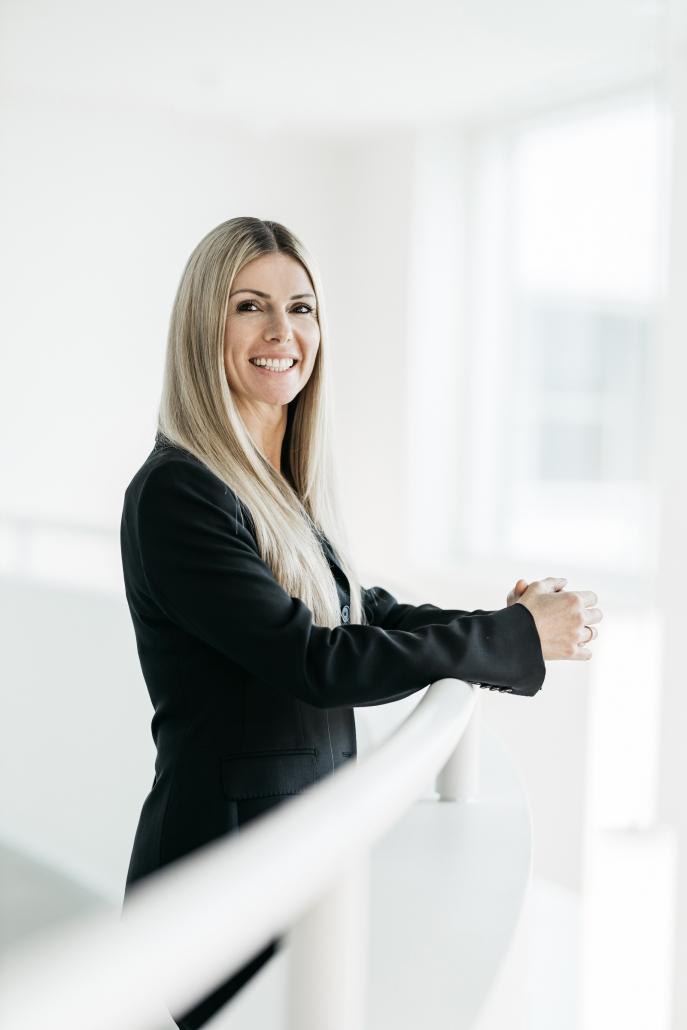 Kathrin Buvac steht an einer weißen Galeriebrüstung und schaut lächelnd in die Kamera.