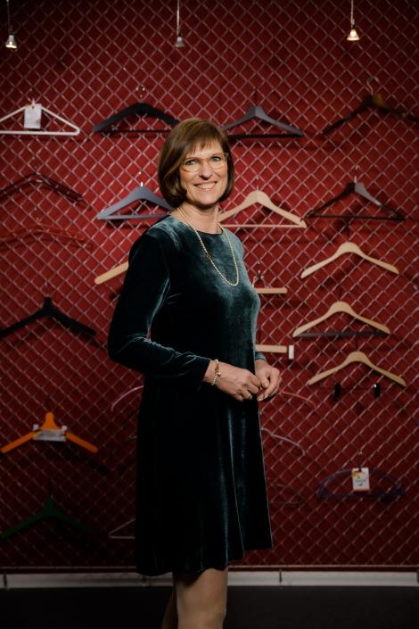 Michaela Schenk steht vor einer Wand mit Kleiderbügeln der MAWA GmbH.