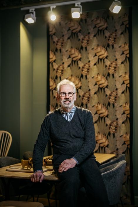 Peter Seidlein lehnt an einem Tisch vor einem gemusterten Wandteppich.