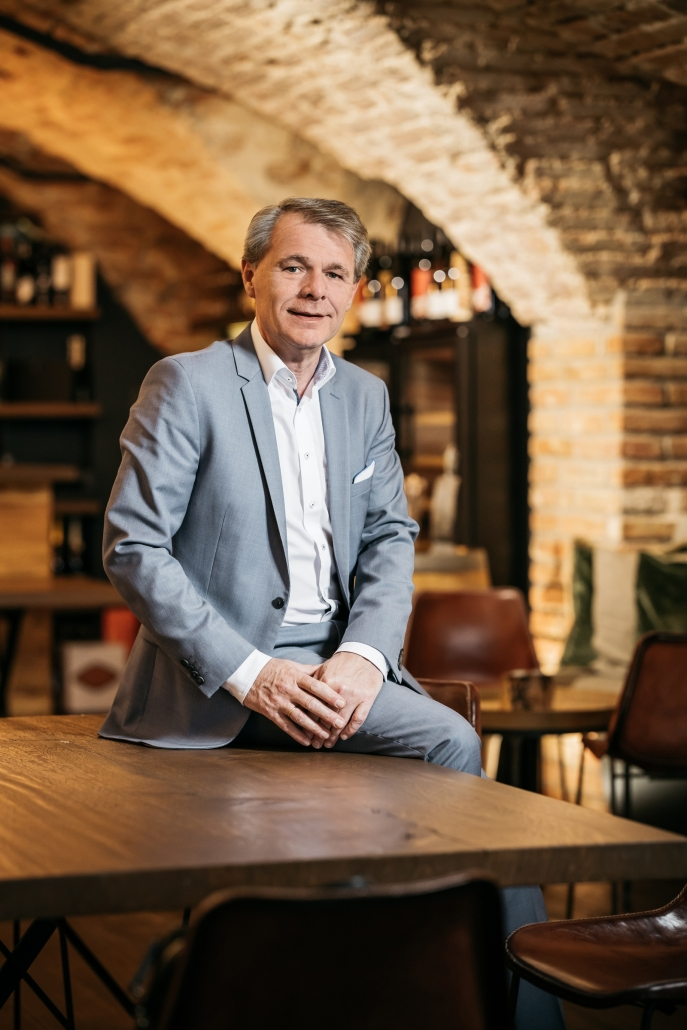 Thomas Edelkamp sitzt auf einem Tisch in einem Raum mit Rundbögen aus Backstein.